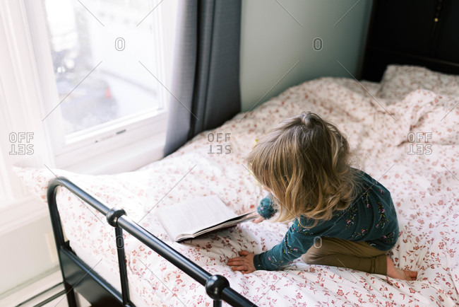 Little girl playing on her bed and reading a book.