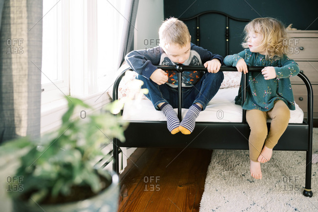 Siblings playing on a bed together happily while in the house.