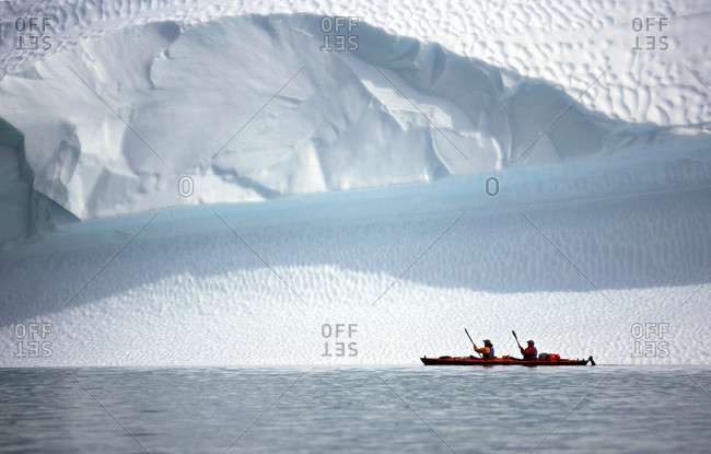 Two men rowing their sea kayak along an iceberg in Greenland