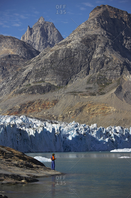 Man standing at the water's edge of a fjord in Greenland