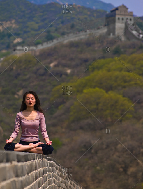 Chinese woman meditating on the Great Chinese Wall