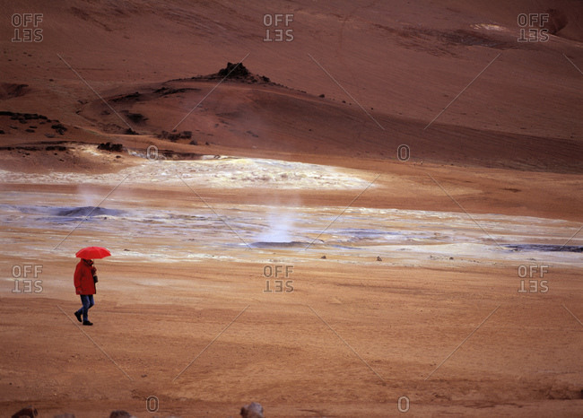 Woman walking with red umbrella at Namskard geothermal hot spring area