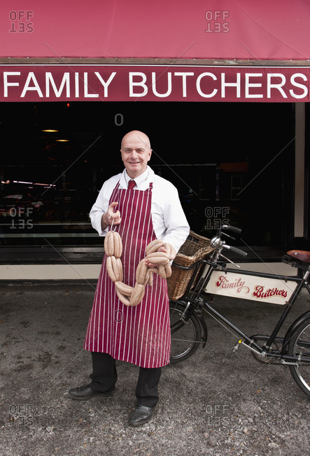 Butcher holding sausage in front of his shop