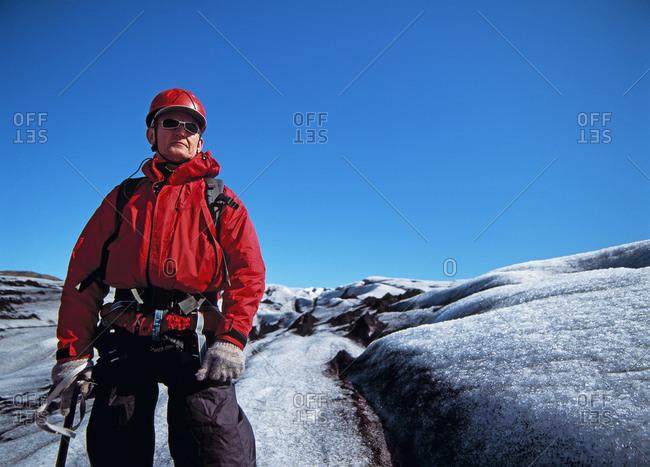 Older man exploring the glacier Solheimajokull in Iceland