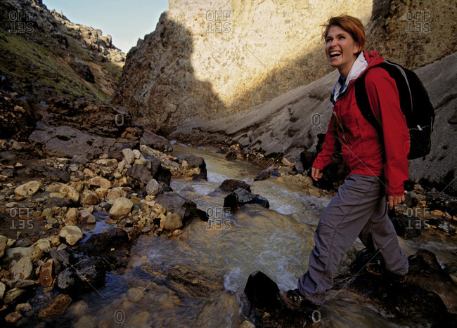 Mature woman crossing stream in Landmannalaugar