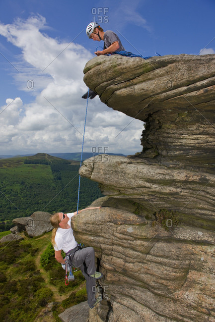 Two friends are climbing at Stanage edge  in the Peak District