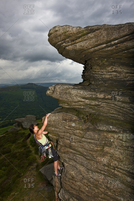 Female rock climber on cliff at the Peak District in England