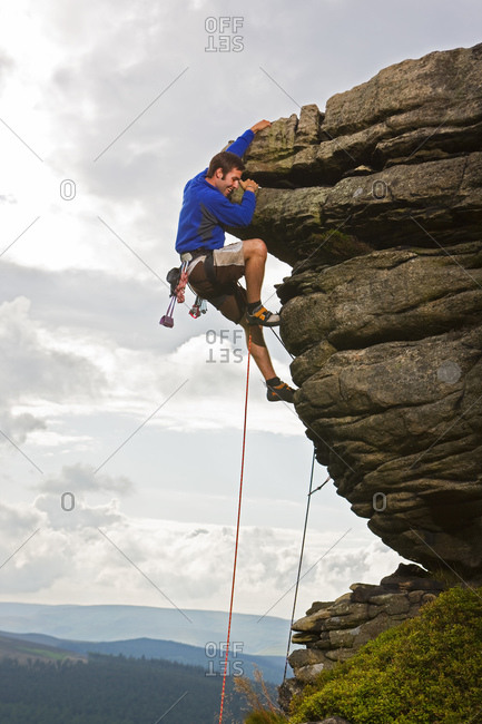 Rock climber on cliff at the Peak District in England
