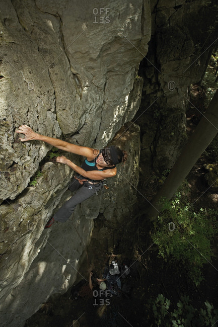 Mature woman climbing limestone cliff in North Germany