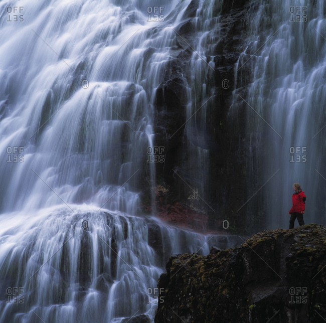 Woman admiring Dynjandi waterfall in the remote fjords of Iceland