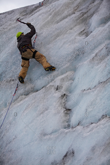Young man climbing ice wall at Solheimajokull glacier in Iceland