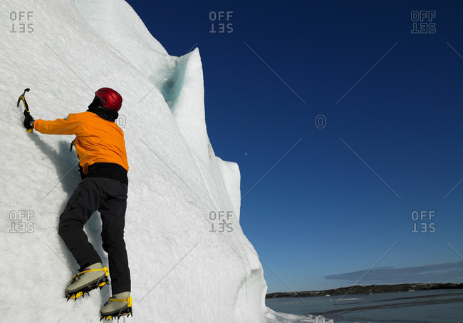 Man climbing up side of a glacier in the south of Iceland
