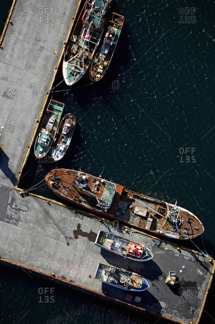 Aerial shot of fishing boats docked on pier in the harbor of Keflavik
