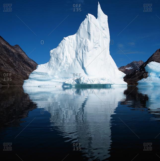 Iceberg floating in still fjord in east Greenland