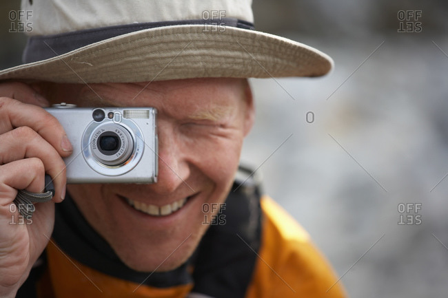 Man taking picture with digital point and shoot camera in Greenland