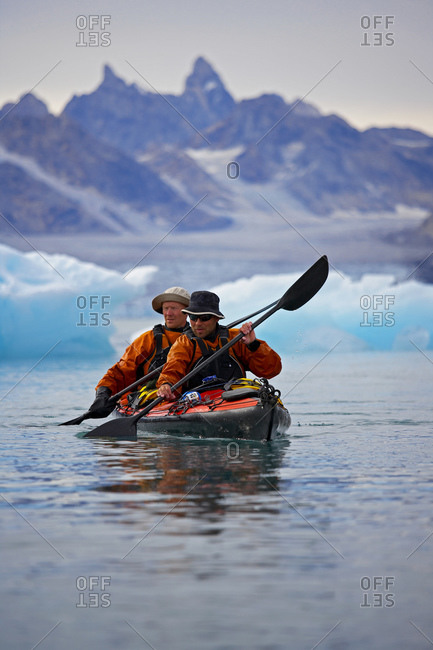 2 men traveling on a sea-kayak though the fjords of eastern Greenland