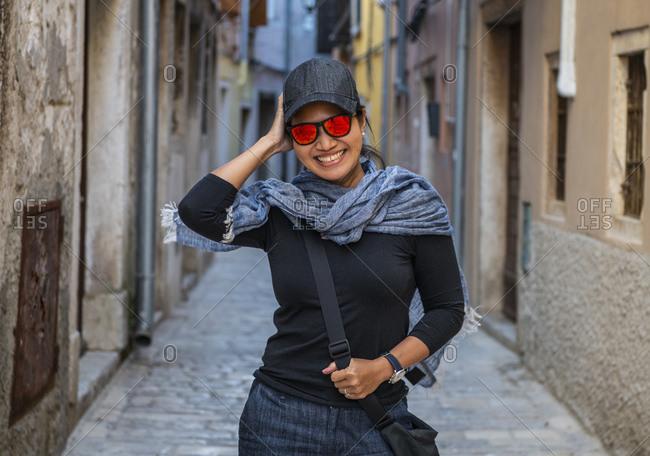 Woman wearing baseball cap and orange sunglasses in street alley