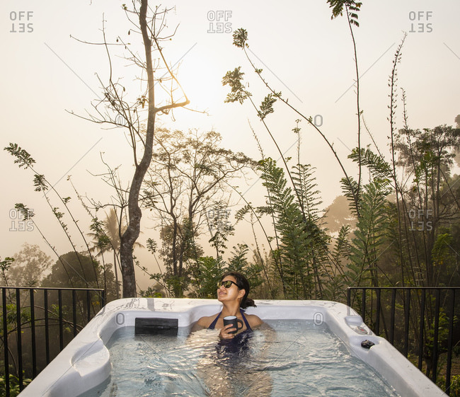 Woman enjoying a bath in a hot tub in the Sri Lankan highlands