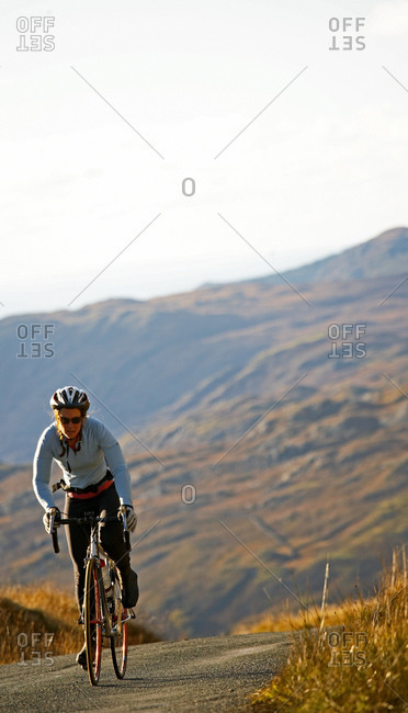 Female cyclist approaching top of a hill at the British Lake district