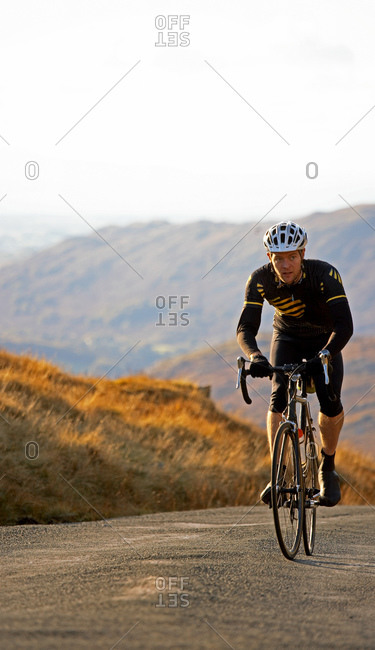 Cyclist approaching top of hill in the British Lake District