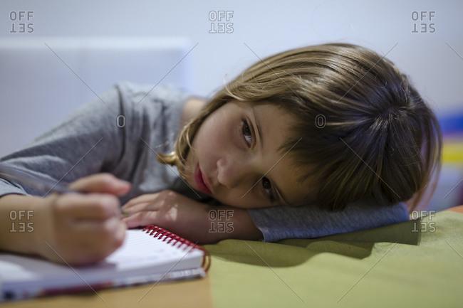 Blonde girl doing her homework in the notebook