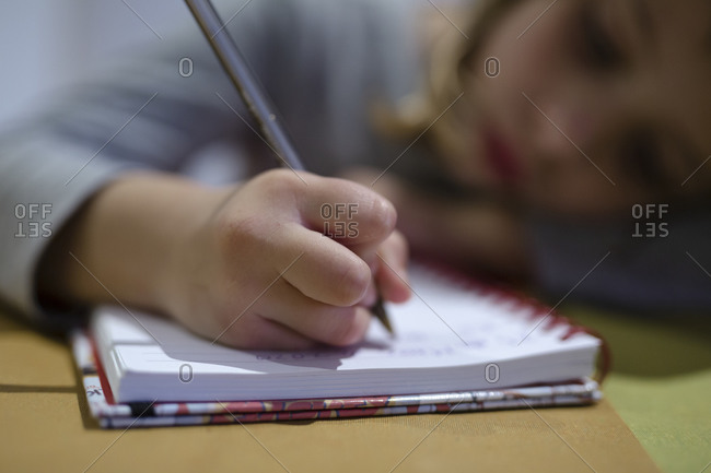 Close-up of girl's hand doing homework in the notebook