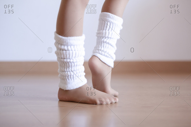 Closeup of unrecognizable girl putting on leg white warmers during ballet practice in studio, copy space