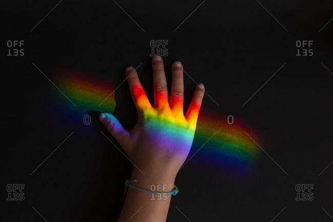 Child's hand on rainbow ray