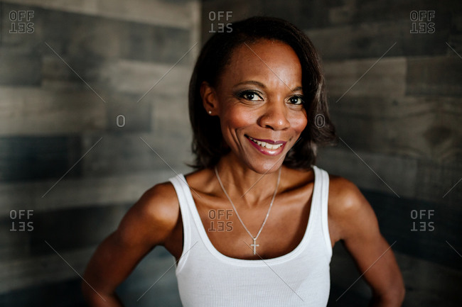 Beautiful slender black woman in white tank top with cross necklace