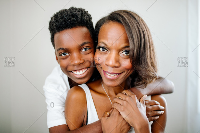 Happy son hugging pretty African American mom from behind