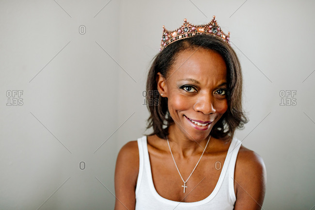 Smiling Black woman wearing tiara, tank top and cross necklace.