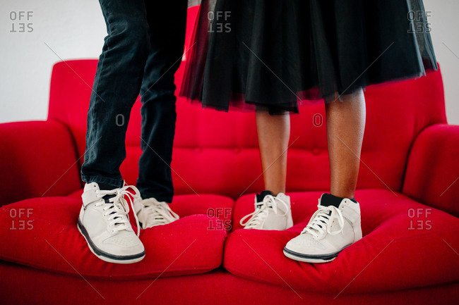 Lower legs of male & female in white sneakers standing on red couch