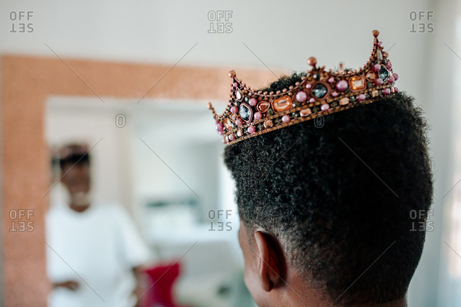 African-American boy wearing jeweled crown looking in mirror