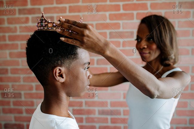 African American mom places crown on serious preteen son