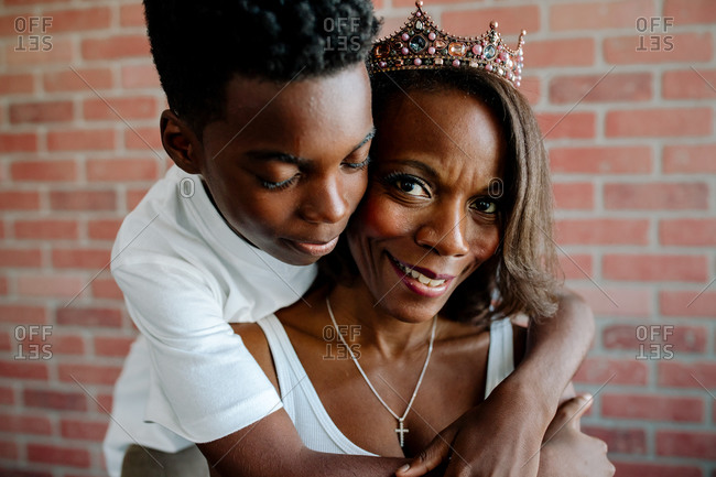 Tender preteen son hugging beautiful Black mom wearing tiara
