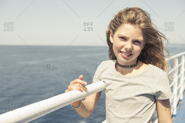 Blond haired girl on windy pier, Portoferraio, Tuscany, Italy