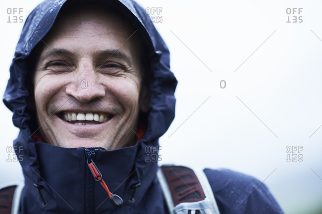 Mature male hiker in hooded anorak in rain, Manigod, Rhone-Alpes, France