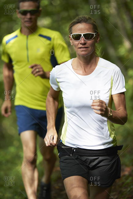 Two joggers running in the forest