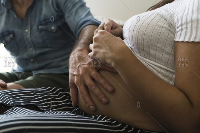 Pregnant couple feeling belly on sofa
