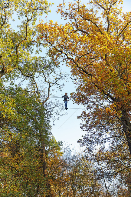 Girl on high rope course, Paris, Ile-de-France, France
