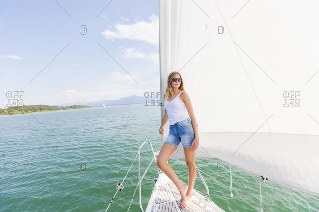 Young woman on sailboat on Chiemsee lake, Bavaria, Germany