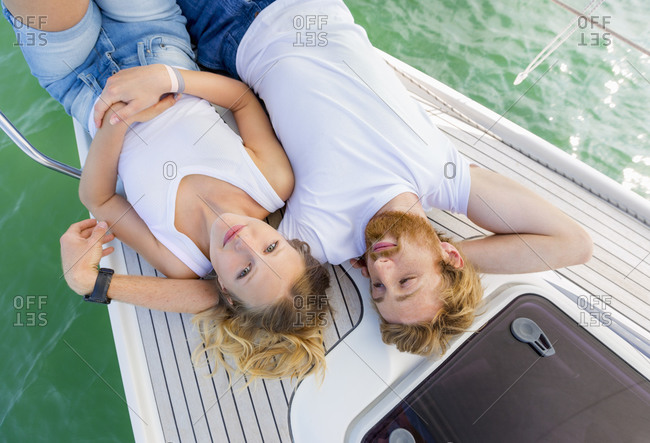 Young couple lying on sailboat on Chiemsee lake, overhead portrait, Bavaria, Germany