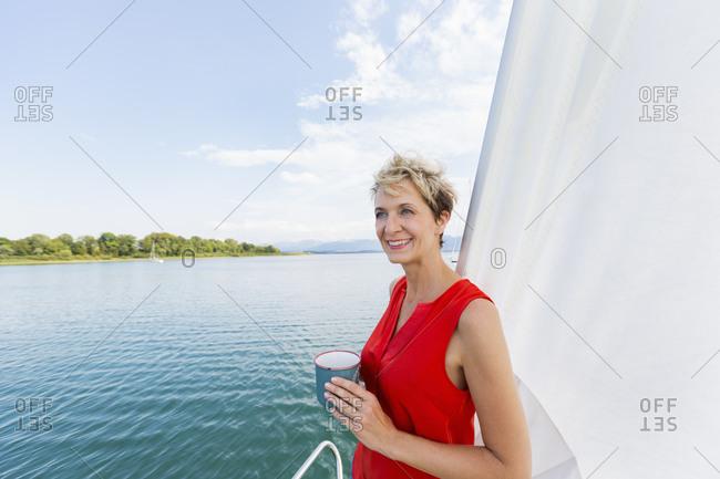 Mature woman having coffee while sailing on Chiemsee lake, Bavaria, Germany