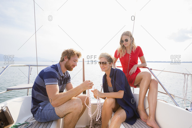 Young man and adult women tying rope knots on sailboat on Chiemsee lake, Bavaria, Germany