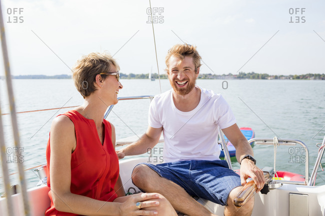 Young man and mature woman laughing on sailboat on Chiemsee lake, Bavaria, Germany