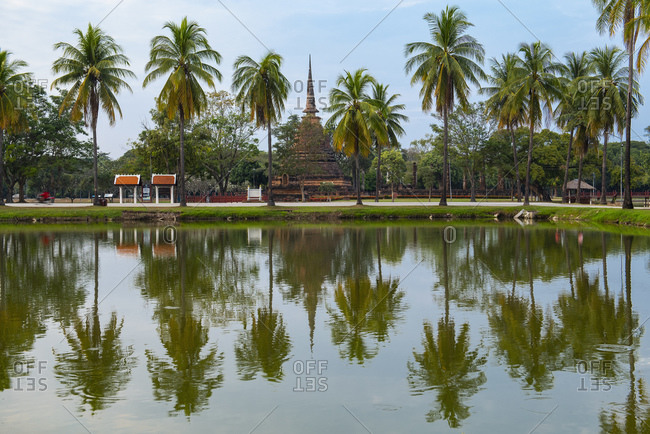 Ancient buddhist temple beyond lake and palms, Sukhothai historical park, Sukhothai, Thailand