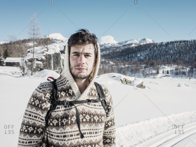 Mid adult man in hooded sweater in snow covered mountain landscape, Alpe Ciamporino, Piemonte, Italy
