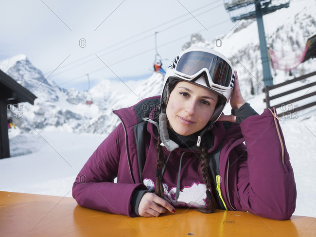 Young woman skier at table in snow covered landscape, Alpe Ciamporino, Piemonte, Italy