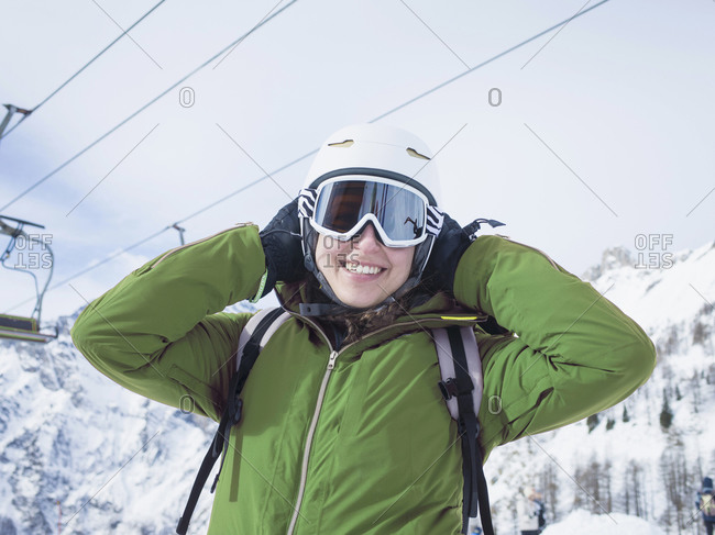 Young woman skier wearing helmet and ski goggles in snow covered landscape,  portrait, Alpe Ciamporino, Piemonte, Italy