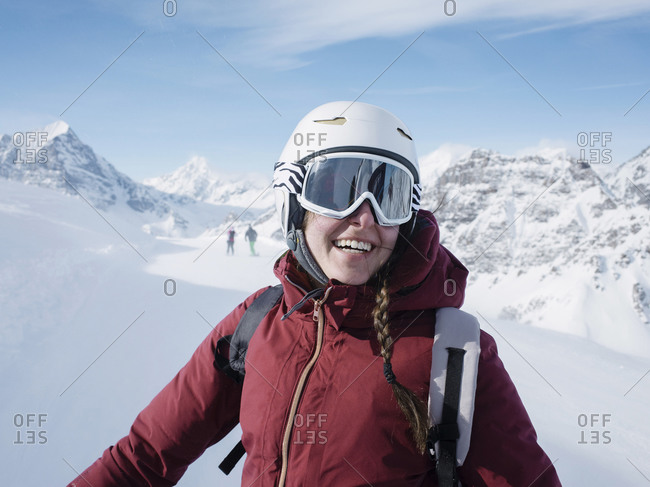 Young woman skier wearing helmet and ski goggles smiling in snow covered landscape,  portrait, Alpe Ciamporino, Piemonte, Italy